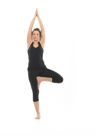 vriksasana: frntal view of young woman sitting in yoga posture, dressed in blak, on white background