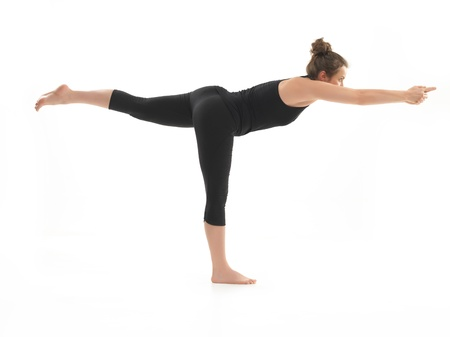 warrior pose: young, beautiful girl demonstrating difficult yoga posture, dressed in black, on whie background