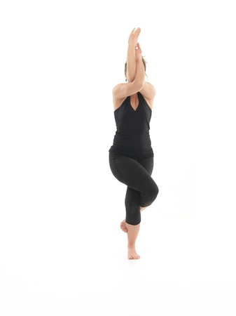 blak and white: young woman sitting in difficutl yoga pose, full frontal view, face obscured, dressed in blak, on white background