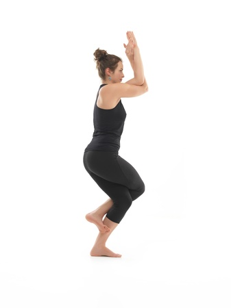 introversion: side view of young woman sitting in difficult yoga pose, dressed in blac, on white background