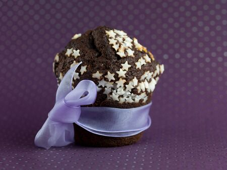 single chocolate muffin, decorated with white sugar stars, wrapped up with a ribbon, on a purple polka dots paper photo