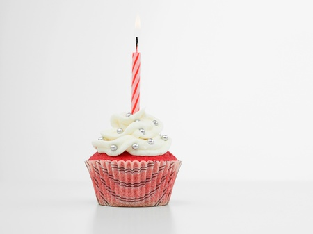 birthday candle: red muffin with cream  white and candy silve one red spiral burning candle on white background isolated