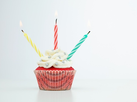 red muffin with three lit candles isolated on white background photo