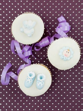 three muffins for newborns with holiday decorations purple ribbon on purple background with dots photo