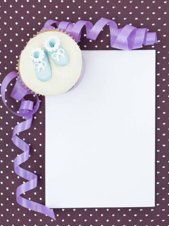 muffin with   blue slippers in corner white frame paper  decorative and purple ribbon photo