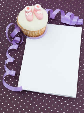 baby arrival: muffin with  pink slippers in corner white frame paper  decorative and purple ribbon