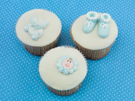 three muffins for newborns with blue decorations  on blue background with dots photo