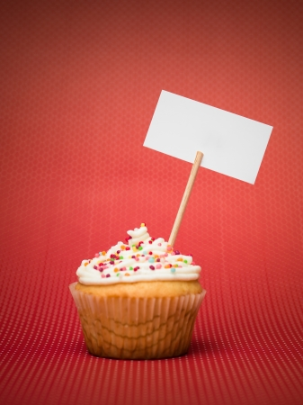 muffin with colorful candy on the table red with white dots and blank sign board gradient red background photo