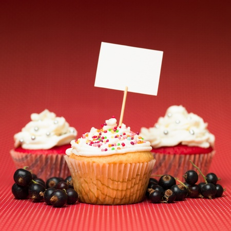 muffins with colorful candy on the table red with white dots and blank sign board gradient red background blackcurrant fruits photo