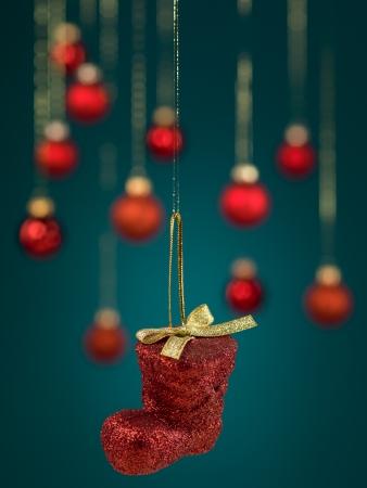 red glittery: closeup di appendere decorazione scintillante rosso di avvio con l'arco, con fili d'oro su sfondo blu sfumato con sfocati globi rossi