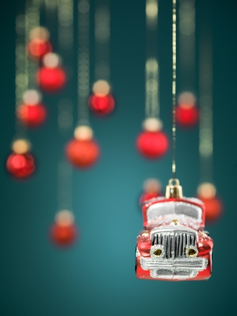closeup of hanging christmas small car decoration with golden strings on blue gradient background with blurred red globes