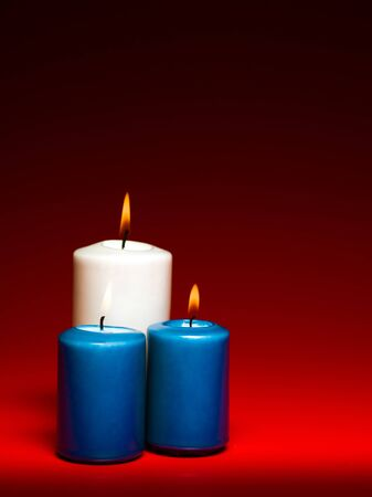 closeup of a group of three burning candles on red background Stock Photo - 16775134