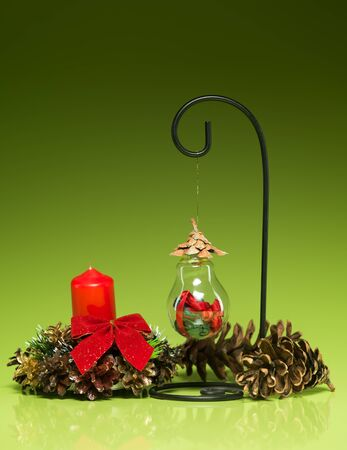 closeup of hanging handmade christmas globe made from recycled materials on a stand with red candle and cones arround it, on green gradient background photo