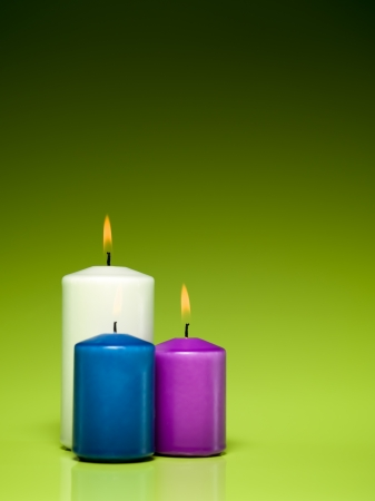 closeup of a group of three burning candles on green gradient background Stock Photo - 16775356