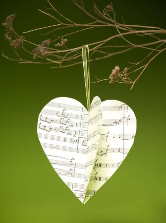 sofisticated: closeup of handmade christmas heart decoration made out of musical scores hanging from a sofisticated branch on green backdrop