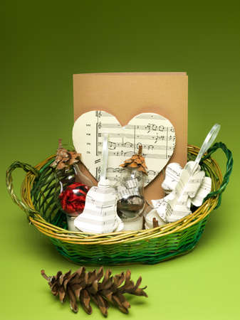 musical score: closeup of gift basket with christmas decorations made out of recycled materials on green background