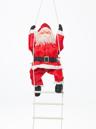 closeup of happy toy santa climbing a plastic and rope ladder isolated on white Stock Photo - 16775545