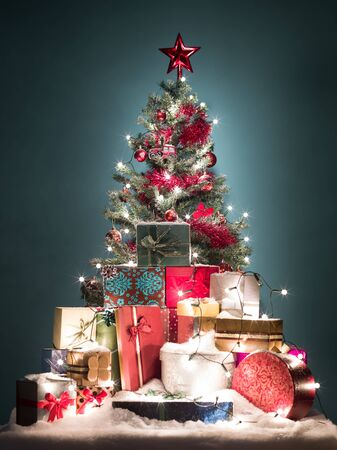 green christmas tree with beatiful red decorations surrounded by a heap of gift boxes covered with snow o blue gradient background photo