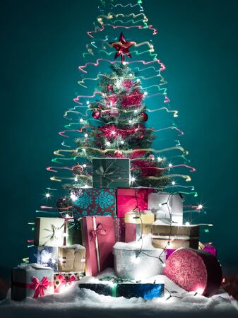 beautifully decorated christmas tree with a pile of shiny and glittery gift boxes in front, surrouned by colorful lights in shape of christmas tree, on blue background photo