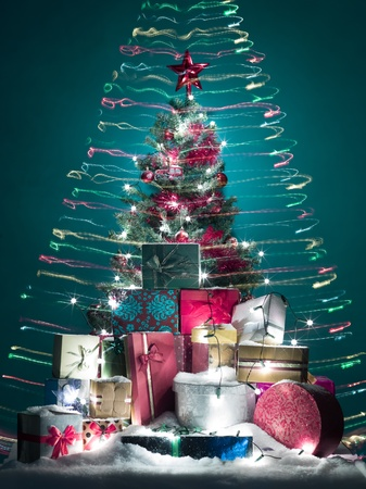 wrapped gift: christmas tree beautifully decorated with red globes, tinsels and star with a stack of shiny presents in front of it covered with snow, surrounded with colorful lights in shape of a cone