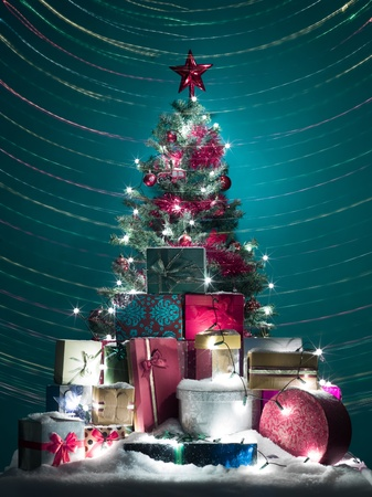 christmas tree beautifully decorated with red globes, tinsels and star with a stack of shiny presents in front of it covered with snow, surrounded with colorful lights photo