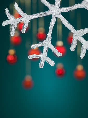 macro of artificial snowflake with red colored hanging christmas globes on blue background photo