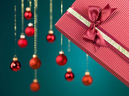 red glittery: primo piano del contenitore di regalo unico con graziose decorazioni su di esso con il Natale globi scintillanti rossi su sfondo blu