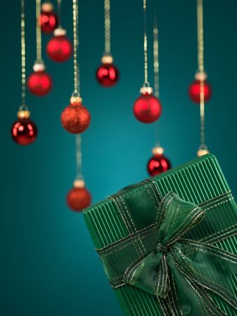 closeup of single green gift box tied with a glittery ribbon and bow with red christmas globes on blue background photo
