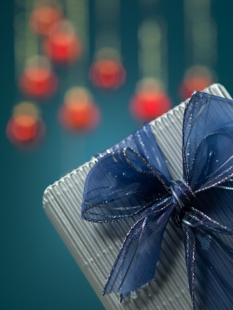 closeup of tiny grey present with blue bow and glitter framed in the lower right corner of the image on blue background photo