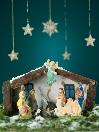 bethlehem crib: closeup of birth of baby jesus scene with wooden figurines, snow and stars on blue background