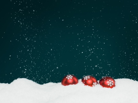 closeup of three red colored christmas globes decorated with glittery snowflakes surrounded with snow, on blue background with falling snowflakes photo