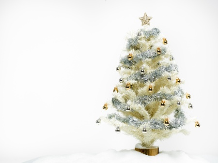 white christmas tree beautifully decorated with shiny golden and silver decorations surrounded with artificial snow isolated on white background photo