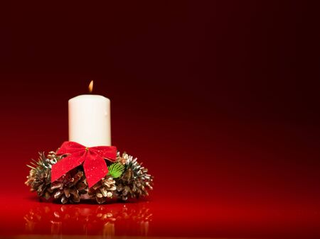 closeup of single white burning candle with beautiful christmas decoration on red background photo