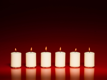 closeup of a group of white burning candles in a row on red background photo