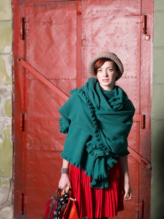 red purse: young red haired caucasian girl with purse, shopping bags and fashionable clothes on street, in front of a red metal door