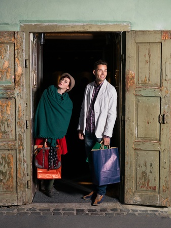 young caucasian couple standing and posing between two opened wooden doors with shopping bags photo