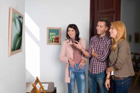 art door: young attractive caucasian people enjoying and art work at a photography exhibition
