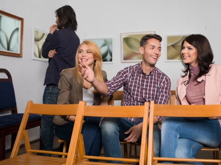 art gallery: young happy people sitting on wooden chairs at an abstract photography exhibition, laughing and pointing at something, with other visitors in background Stock Photo