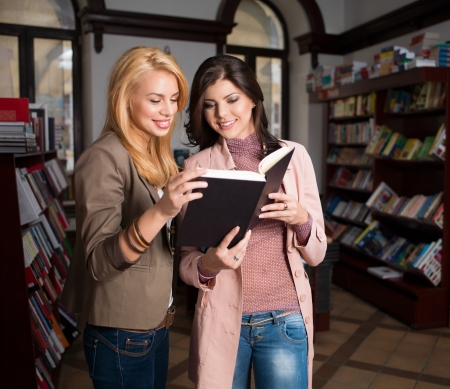 two young beautiful caucasian girls in a bookstore with a black hardcover book in their hands, reading