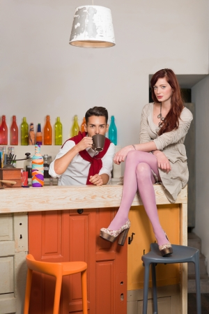 young attractive red haired caucasian girl sitting on the counter with legs and arms crossed with a handsome guy behind the counter drinking coffee, in colorful cafe photo
