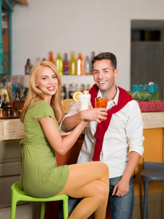 sexy lovers: close-up of young beautiful caucasian couple drinking cocktails at the counter in colorful cafe