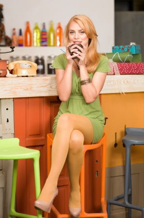 young attractive blonde girl sitting on a chair with her legs crossed near the conter of a colorful cafe with a coffee mug in her hands photo