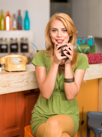 young attractive blonde girl sitting on a chair near the conter of a colorful cafe with a coffee mug in her hands, smiling photo