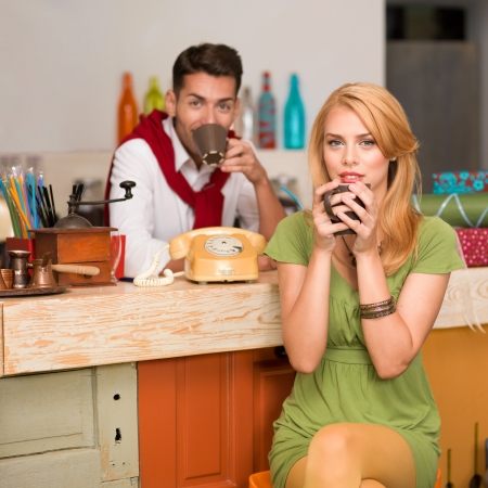 close-up of beautiful blonde girl drinking a coffee and a handsome guy behind the counter in a cafe photo