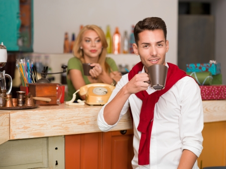 close-up of young handsome caucasian guy smiling with a coffee mug in his hand with a blonde girl behind the counter of a colorful cafe photo