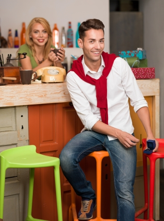 handsome caucasian man sitting on a chair at the counter of a cafe holding a box with an engagement ring in it, with a blonde girl behind the counter photo
