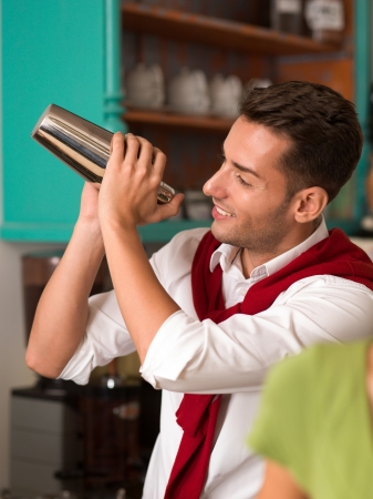 close-up of young handsome bartender preparing a drink with a shaker in a bar photo