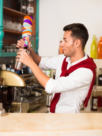 young attractive caucasian bartender pouring beverage from a colorful bottle wrapped in paper into a shaker photo