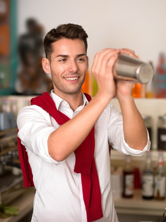 close-up of young caucasian guy preparing a drink with a shaker in a bar photo