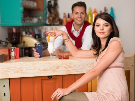 young beautiful caucasian girl sitting at a bar drinking a cocktail an smoking a cigarette with a guy behind the counter photo